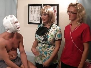 Blonde nurses give a precautionary prostate exam to a patient